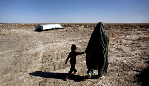 An Iranian woman walks with her daughter past an abandoned boat in Sikh Sar village at Hamoon wetland near the Zabol town, in southeastern province of Sistan-Baluchistan bordering Afghanistan on February 2, 2015. AFP PHOTO/BEHROUZ MEHRI        (Photo credit should read BEHROUZ MEHRI/AFP/Getty Images)