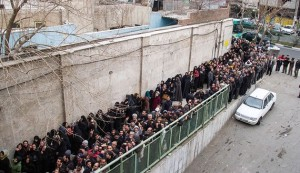 A picture taken on February 3, 2014 shows low-income Iranians lining up to receive food supplies in southern Tehran. Iranian President Hassan Rouhani faced harsh criticism from conservatives today over what they say is a poorly implemented scheme to distribute food to low-income families in the sanctions-hit Islamic republic. The programme aims to hand out packages of frozen chicken, rice, vegetable oil, cheese and eggs to poor families ahead of Iranian New Year celebrations in mid-March.  AFP PHOTO/ISNA/DAVOUD GHAHRDAR        (Photo credit should read DAVOUD GHAHRDAR/AFP/Getty Images)