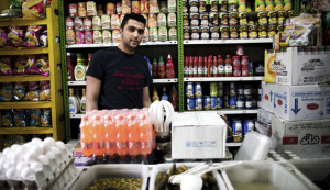 TO GO WITH AFP STORY BY ARTHUR MACMILLAN Iranian Ali Heydari, 22, poses at his grocery in southern Tehran on April 22, 2014, claiming that prices are still increasing and his sales decreasing. Iran's President Hassan Rouhani was elected on hopes that he could revive the country's sanctions-neutered economy, but the public's goodwill towards him is showing the first signs of fading. AFP PHOTO/BEHROUZ MEHRI        (Photo credit should read BEHROUZ MEHRI/AFP/Getty Images)