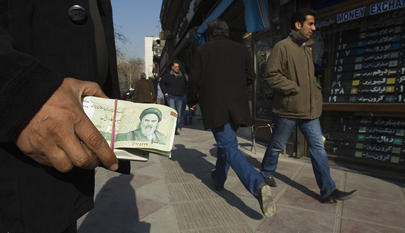 EDITORS' NOTE: Reuters and other foreign media are subject to Iranian restrictions on leaving the office to report, film or take pictures in Tehran.  A money changer holds Iranian rial banknotes as he waits for customers in Tehran's business district January 7, 2012. REUTERS/Raheb Homavandi  (IRAN - Tags: BUSINESS) - RTR2VZCL