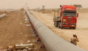 Workers set up a natural gas pipeline during a dust storm at Iraq's border with Iran in Basra, southeast of Baghdad, April 12, 2016.  REUTERS/Essam Al-Sudani - RTX29NH6